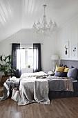 Tagesdecke und Kissen auf Boxspringbett mit Kopfteil in Schlafzimmer mit weisser Holzverschalung
