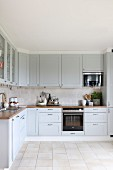 Fitted kitchen with pale grey cupboards and beige tiled floor
