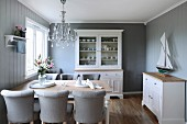 Pale grey upholstered chairs around wooden table in traditional, Scandinavian-style dining room