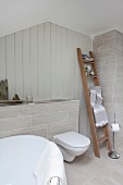 Pale grey tiles on floor and false wall in bathroom with towels on ladder next to toilet