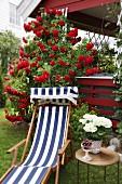 Liegestuhl mit blau-weißem Streifenbezug und Beistelltisch im Garten vor Veranda mit roten Kletterrosen