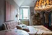 Bett mit gepolstertem Kopfteil und kunsthandwerklicher, beleuchteter Lampenschirm im Schlafzimmer