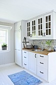 Fitted kitchen with white cupboards and black handles in country-house style