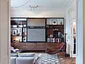 Fitted cabinet with shelves and sliding elements and retro leather armchair in elegant living room