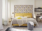 An elegant, feminine double bed with a light plaid and yellow cushions against a floral-papered frame at the head end