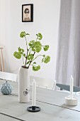 Delicate green flowers in white vase and candles on wooden table