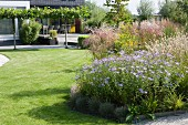 Herbaceous borders and mown lawn in well-tended garden