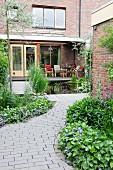 Gepflasterter Weg zum Backsteinhaus mit Terrasse und Teich