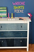 White chest of drawers with drawer fronts covered in denim