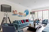 Zwei Stehleuchten mit transparentem Lampenschirm neben blauem Sofa und Kunstobjekt als Wanddekoration in elegantem Loungebereich