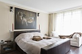 Double bed with leather-covered headboard and foot below picture of zebra in elegant bedroom