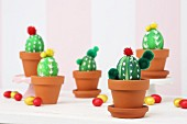 Blown eggs, painted and decorated as cacti in terracotta pots amongst scattered chocolate eggs