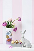 Concrete hare, Easter ornaments and vase of tulips against striped wallpaper