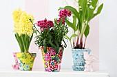 Mit buntem Sfoff verzierte Tontöpfe mit Frühlingsblumen
