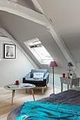 Sessel und Dreibeintisch unter dem Dachfenster im Schlafzimmer