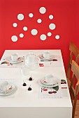 Table set for afternoon coffee with cherries against red wall decorated with white doilies