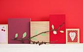 Wanddekoration mit Kirschblütenzweig vor unterschiedlich gestalteten Holztafeln