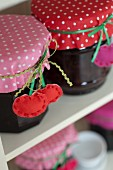Jars of jam decorated with hand-sewn cherry tags an polka-dot fabric covers