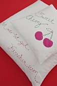 Hand-made scatter cushions with embroidered mottos and cherry motif