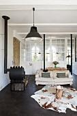 Loungebereich mit Tierfellteppich, Baumstumpf-Tisch und Kaminofen vor Innenfenster