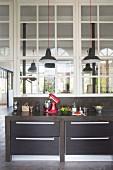 Betonierte, schwarze Küchenzeile mit Schubladen und Küchenutensilien vor Innenfenstern mit Loft-Charakter