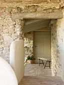 Rustic bench and potted geranium in entrance to stone house