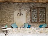 Gemauerte Sitzbank aus Naturstein mit Kissen unter verziertem Fensterladen