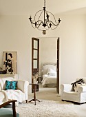 Helle Lounge mit Polstermöbeln, Blick durch Flügeltür ins Schlafzimmer