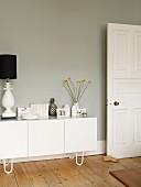 Weisses Sideboard mit Vasen, Büchern und Tischleuchte vor grauer Wand in Altbauwohnung mit Dielenboden
