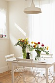 Colourful flowers on simple, white dining table and folding chairs next to window