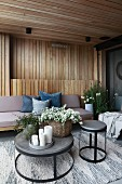 Upholstered furniture and round tables on wood-panelled modern terrace