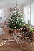 Geschmückter Weihnachtsbaum mit traditioneller Weihnachtskrippe auf Vintage Holzschlitten