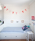 White bed with storage drawers and blue and white bed linen in Scandinavian-style boy's bedroom
