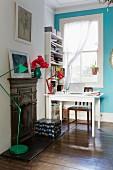 Weisser Tisch mit Holzstuhl vor Sprossenfenster und türkisblauer Wand
