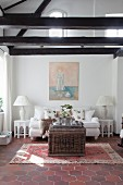 White sofa in lounge of renovated farmhouse with exposed beams
