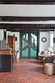 Grüne Flügeltür im Dielenbereich mit Korbsesseln, Antikmöbeln und Terrakottafliesenboden in renoviertem Bauernhaus