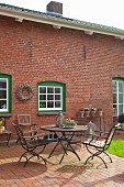 Summery terrace outside renovated brick house with white lattice windows in green frames