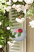 Romantic, knitted lantern decorated with knitted flowers below white climbing rose in front of external shutters
