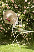 Flower arrangement and romantic straw hat on vintage garden chair in front of pink climbing rose