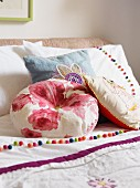 Various scatter cushions on white bed linen