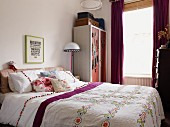 Double bed with ethnic bedspread, scatter cushions and white bed linen with pompoms next to wardrobe