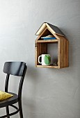 Books, cup and glasses on hand-made, wooden, house-shaped shelf next to chair
