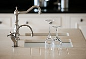 Washed wine glasses on Silestone kitchen worksurface next to sink with vintage tap fittings