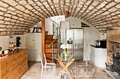 Rustic vaulted ceiling, white fitted furniture and winding wooden staircase in large kitchen