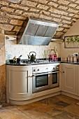 weiße, abgerundete Landhausküche mit Gasherd und Dunstabzug an rustikaler Naturstein-Gewölbedecke