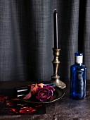 Dark purple rose on dish, blue glass bottle and brass candlestick in front of black curtain