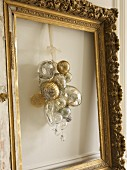 Silver and gold Christmas baubles hung in empty picture frame