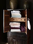 Stacked table linen in dark wooden cupboard with open door