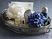 Blue hydrangea flower in small vase, alarm clock and salt cellar on silver tray