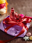 Red bird ornament on gift wrapped with ribbon
